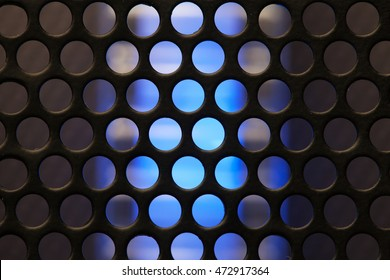 Blue glow of a high performance server, operating behind a metal mesh or grid. Abstract background. Focus on Mesh of Grid. Shallow depth of field.