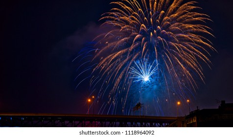Blue and gold fireworks burst above a highway bridge in Cleveland, Ohio