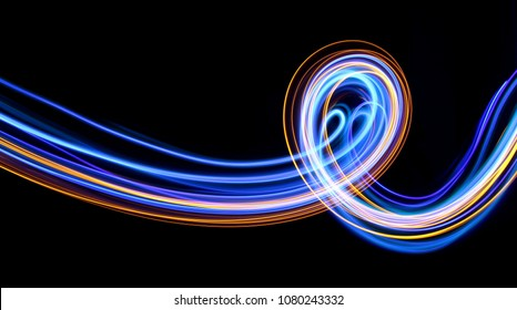 Blue and gold light painting, long exposure photography, abstract swirls and loops against a black background