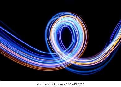 Blue and gold light painting photography, long exposure fairy lights curves and loop against a black background