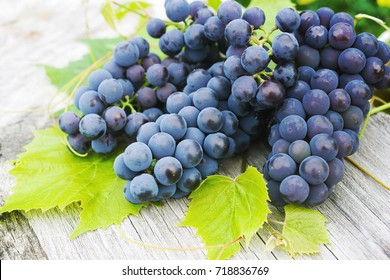 Blue grapes and bright grape leaves on an old wooden surface, close up.
