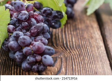 Blue Grapes (detailed close-up shot) on wooden background