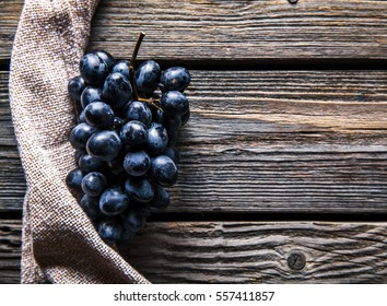 Blue grapes with a kitchen towel on wooden background. Food, Fruits