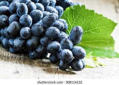 Blue grapes with leaves on old wooden background, selective focus