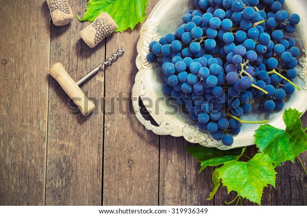 blue grapes in a metal bowl on a wooden background