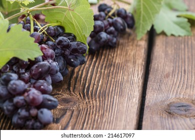 Blue Grapes (on wooden background) as detailed close-up shot