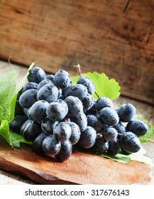 Blue grapes with vine on the old wooden background, selective focus