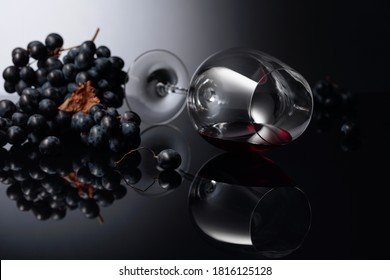 Blue grapes and wine glass with red wine on a black reflective background. Copy space.