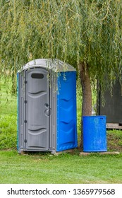 Blue and gray chemical toilet on outdoor spot