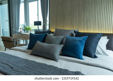 Blue and gray cushion in master bedroom with modern furniture by the window.