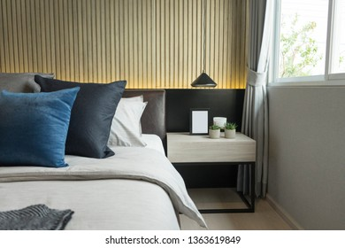 Blue and gray cushion in master bedroom with plant pot and picture frame by the window.