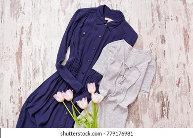 Blue and gray dress, pink tulips on a wooden background. Fashionable concept, top view