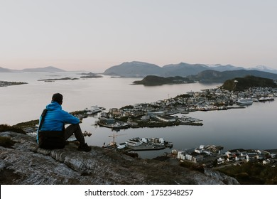 Blue and gray dressed solitary traveller is looking at the norwegian city from the cliff. Travel and hiking concept. Shot during the blue hour.