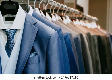 Blue and gray men suit jackets on hanger in a shop