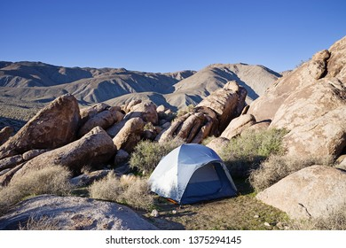 blue gray tent set up in the desert between rocks in Death Valley National Park