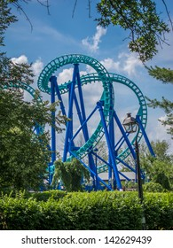 Blue and green amusement park roller coaster amongst green trees against a vivid blue sky