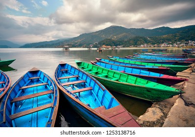 Blue and green boats at Phewa lake shore in Pokhara, Nepal.