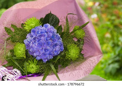 Blue and green bouquet of flowers wrapped in paper with summer garden background