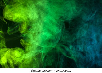 Blue and green  cloud of smoke of  black isolated background. Background from the smoke of vape