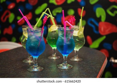 Blue and green cocktail in a glass with ice and a straw on the table.