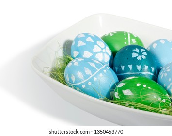 Blue and green Easter eggs on white plate