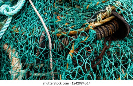 Blue and Green Fishing Net with ropes on a pile in Lymington, England.