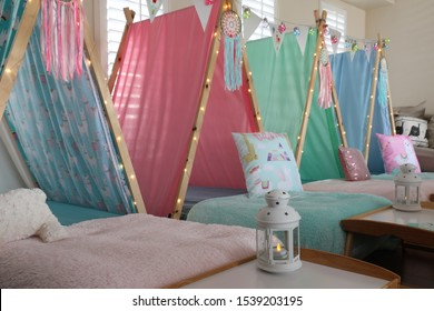 Blue, green, pink and lama teepee's all set up for a sleepover birthday party.  There is also fairy lights, bunting and face masks .