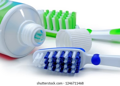 Blue, green plastic toothbrushes and toothpaste are isolated on a white background. Macro studio shooting