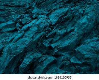 Blue green rock background. Dark turquoise toned mountain surface. Cracked. Close-up. 3d effect. Modern colorful stone background with copy space for your design.