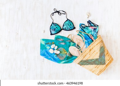 Blue and green swimsuit with tropical print, beige flip flops and straw wicker beach bag on white wooden background. Overhead view of woman's swimwear and beach accessories. Flat lay, top view.