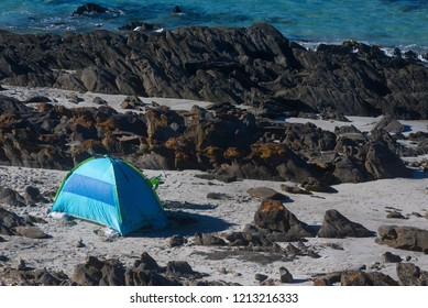 Blue and green tent surrounded by rocks on sandy beach.
