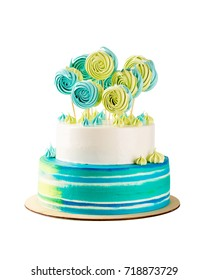Blue and green tiered birthday cake isolated on white. Big homemade cake decorated with colorful meringues