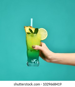 Blue and green tropical alcohol cocktail drink with pineapple in woman hand on mint background