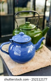 Blue and Green vintage tea pots on an oven outdoors in the backyard