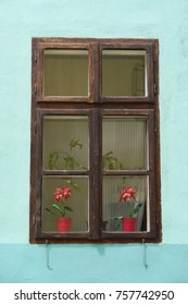 Blue green wall of a romanian house with a wooden window and flowers on a sunny summer day