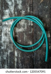 blue green water hose on plank floor