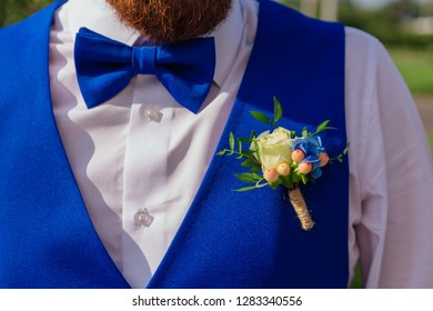 Blue groom's bow tie and flowers on waistcoat close up