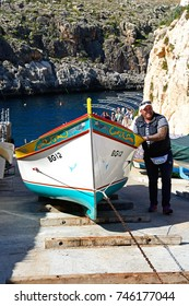 BLUE GROTTO, MALTA - APRIL 1, 2017 - Man pulling a traditional Dghajsa water taxi up a ramp for mooring at the departure point, Blue Grotto, Malta, April 1, 2017.