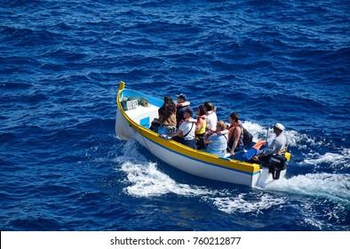 BLUE GROTTO, MALTA - APRIL 1, 2017 - Tourists in Dghajsa water taxi boat in the bay, Blue Grotto, Malta, Europe, April 1, 2017.
