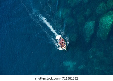 BLUE GROTTO, MALTA - AUGUST 23, 2017: Tourists taking a boat trip at the Blue Grotto. The sea caves of Blue Grotto and natural arch are one of the major tourist sights of Malta