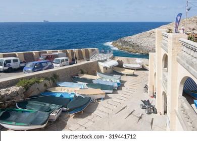 BLUE GROTTO, MALTA - SEPTEMBER 15, 2015: Boats lying along the downhill street of popular tourist attraction Blue Grotto on a sunny day in September 15, 2015 in Malta.
