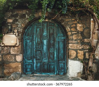 Blue grunge wooden door in brick wall
