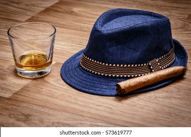 blue hat with cigar and expensive drink of whisky or rum on wooden floor. Gentleman relax concept