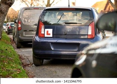 Blue hatchback car with a learner driver sign at the rear, parking at the side of the road, parking training, parallel parking