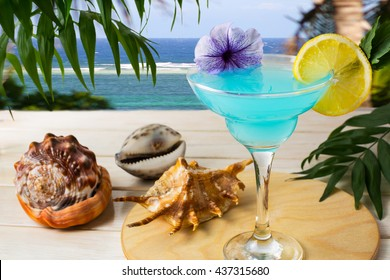 Blue Hawaiian cocktail on the tropical sea background. Iced blue cosmopolitan cocktail. Blue Lagoon cocktail. Blue margarita. Blue curacao liqueur. Iced blue cosmopolitan. Summer drink.