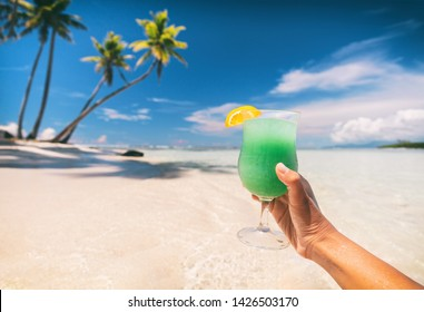 Blue Hawaiian drink cocktail woman drinking curacao liqueur on beach vacation travel in Caribbean destination. Summer fun lifestyle.