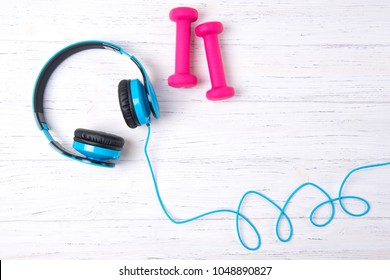 Blue headphones and pink dumbbell on wooden background, fitness
