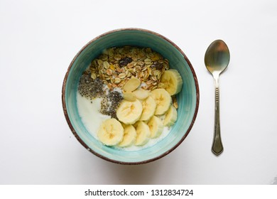 Blue healthy breakfast bowl with musli banana chia seeds and yoghurt with spoon isolated on white bacground