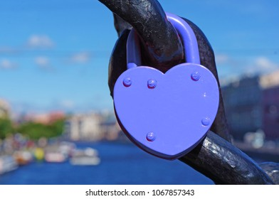Blue heart shaped lock, canal with boats on the background.