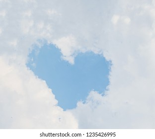 blue heart shaped in many white clouds and blue sky background in love concept.